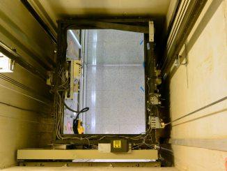 Fahrkorb mit geöffneter Dachluke in einem Aufzugsschacht.